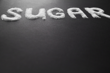 White Sugar Inscription On Table. Close Up Of Word Sugar Written With White Granulated Sugar On Black Background. High Resolution. Imagens - 96944268