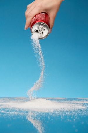 Sugar In Drinks. Hand Holding Soda Can With Sugar. Close Up Of White Sugar Pouring Out Sugar Of Beverage Can. Unhealthy Food Concept. High Quality Image.