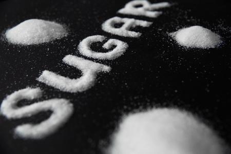 シュガーワード。背景に白砂糖。テーブルの上に白い洗練された砂糖の碑文をクローズアップ。高品質 写真素材