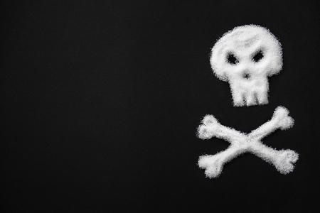 シュガー毒。頭蓋骨とクロスボーンの形で白い砂糖。黒の背景に砂糖のクローズアップ。糖尿病と死の概念。高品質の画像。
