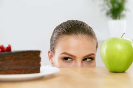 Diet And Nutrition. Healthy Eating Woman Choosing Between Cake And Apple. Portrait Of Beautiful Young Female Thinking Whether To Eat Fruit Or Sweets. High Quality Image. Stock Photo