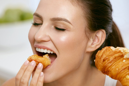 Diet. Happy Woman Eating Croissant For Breakfast.  Portrait Of Beautiful Happy Woman Biting Crunchy Bakery Product, Sweet Pastry. Nutrition Concept. High Resolution.