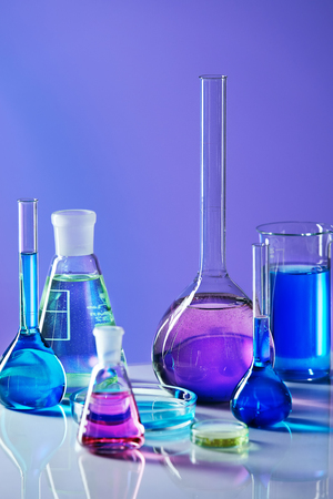 Laboratory Glass With Colorful Liquid. Close Up Of Laboratory Transparent Glassware With Multicolor Fluid On Table In Chemical Lab. Laboratory Equipment. Chemical Research. High Quality Image. Banque d'images