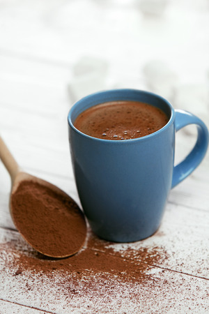 Cocoa Drink. Cup Of Beverage. Close Up Of Blue Mug Of Sweet Hot Drink And Spoon With Cocoa On Table. High Quality Image.