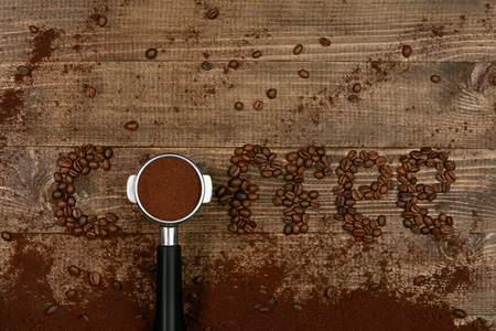 Word Coffee On Wooden Background. Flat Lay Closeup Of Coffee Beans In Form Of Word Coffee With Portafilter With Roast Ground Coffee On Wood Table. Top View. High Quality Image. Stock fotó