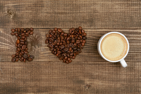 I Love Coffee. Coffee Beans And Cup Of Coffe On Table. Close Up Of Cup Of Aromatic Coffee And Beans In Form Of Heart On Wooden Table. High Quality