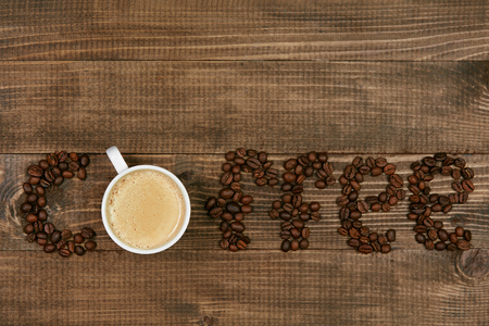 Word Coffee On Wooden Background. Flat Lay Closeup Of Coffee Beans In Form Of Word Coffee And Cup Of Fresh Brewed Americano Coffee On Wood Table. Top View. High Quality Image.