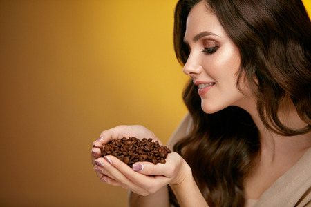 Coffee Beans. Beautiful Woman Smelling Coffee Beans. Attractive Smiling Female With Gorgeous Makeup On Beauty Face And Curly Brown Hair Holding Coffee Beans In Hands, Enjoying Aroma On Gold Background