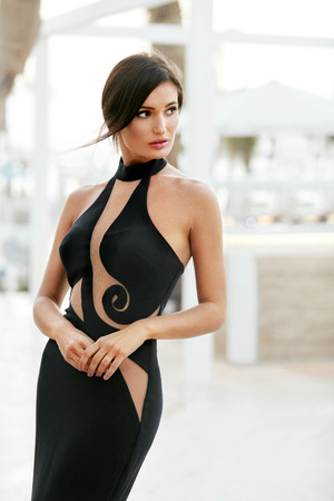 Women Style. Fashion Girl In Long Black Dress Posing Outdoors. Portrait Of Beautiful Fashionable Female Model In Glamourous Evening Dress With Elegant Hairstyle Posing Outdoors. High Quality Image.
