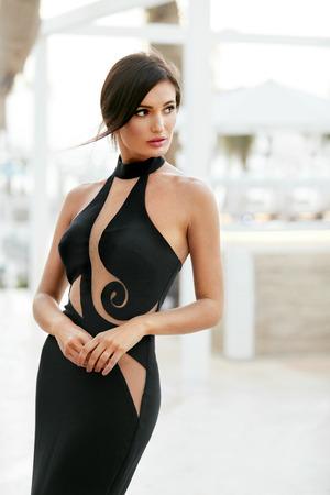 Dames stijl. Mode meisje in lange zwarte jurk buitenshuis poseren. Portret van mooi modieus vrouwelijk model in betoverende avondjurk met elegant kapsel dat in openlucht stelt. Afbeelding van hoge kwaliteit.