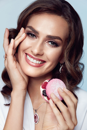 Fashion Woman. Female Model With Beauty Makeup. Portrait Of Sexy Girl With Beautiful Facial Makeup And Stylish Hairstyle Wearing Jewellery Of Precious Stones, Holding Cake In Hand. High Resolution.