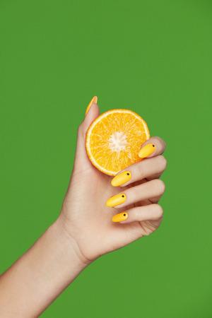 Nagel Design. Hände mit der Mode-Maniküre, die Orange auf grünem Hintergrund hält. Schließen Sie oben von der Frau mit der stilvollen Maniküre, die an Hand Zitrusfrucht hält. Hochwertiges Bild.
