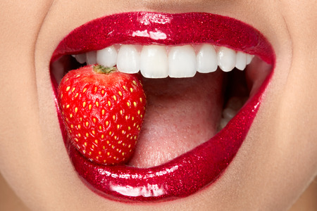 Lips. Woman With Red Lipstick And Strawberry. Close Up Of Plump Full Sexy Lips With Professional Lip Makeup Holding Berry In White Healthy Teeth. Beauty And Cosmetics Concept. High Resolution Stok Fotoğraf - 97761982