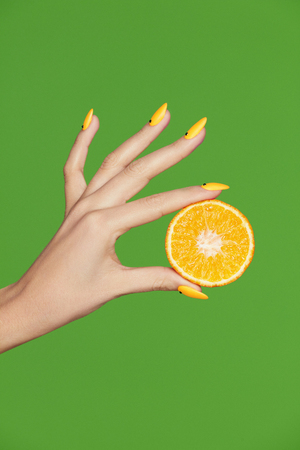 Nails Design. Hands With Fashion Manicure Holding Orange On Green Background. Close Up Of Female With Orange Stylish Manicure On Hand Holding Citrus. High Quality Image.