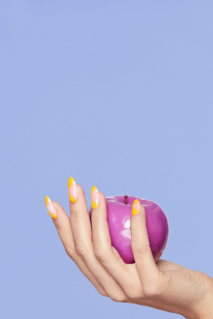Nails Design. Female Hands With Colorful Nails Holding Apple On Violet Background. Close Up Of Woman Fingers With Fashion Orange Manicure Holding Purple Apple. High Quality Image.
