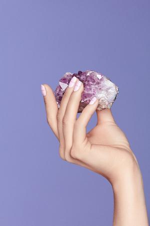 マニキュア。紫色の宝石を持つスタイリッシュな爪で手。バイオレットの背景にバイオレットプレシマンストーンを保持するパステルマニキュアで