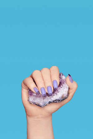 Manicure. Hand With Stylish Nails Holding Purple Gemstone.  Close Up Of Female Fingers With Violet Geometric Manicure Holding Violet Precious Stone On Blue Background. High Quality Image. 版權商用圖片