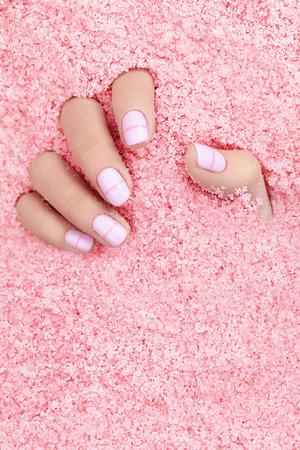 Mains féminines avec des clous dans le sel de mer coloré. Gros plan d'une main de femme avec une manucure blanche au sel de mer rose. Image de haute qualité. Banque d'images