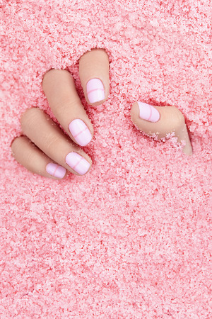 Female Hands With Nails In Colorful Sea Salt. Close Up Of Woman Hand With White Manicure In Pink Sea Salt. High Quality Image.