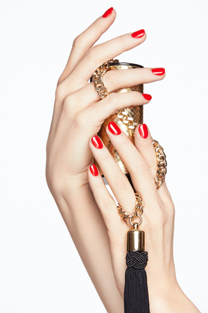 Beauty Nails. Female Hands With Red Manicure. Close Up Of Woman Hands With Red Nail Polish Holding Fashion Purse On White Background. High Resolution.