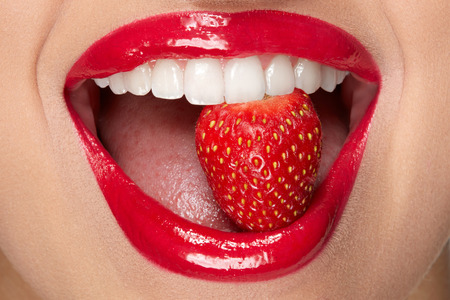 Lips. Woman With Red Lipstick And Strawberry. Close Up Of Plump Full Sexy Lips With Professional Lip Makeup Holding Berry In White Healthy Teeth. Beauty And Cosmetics Concept. High Resolution