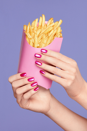 Pink Nails. Female Hands And Fries On Violet Background. Close Up Of Female With Purple Manicure On Hands Holding Pink French Fries. Nail Art. High Quality Image.