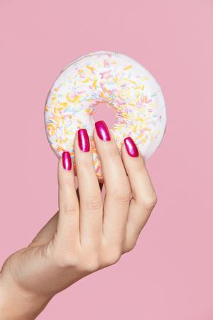 Manicure. Ręka Z Różowymi Gwoździami Trzyma Pączek. Bliska kobieta z różowy manicure uroda, trzymając w ręku słodki pączek na różowym tle. Obraz wysokiej jakości. Zdjęcie Seryjne