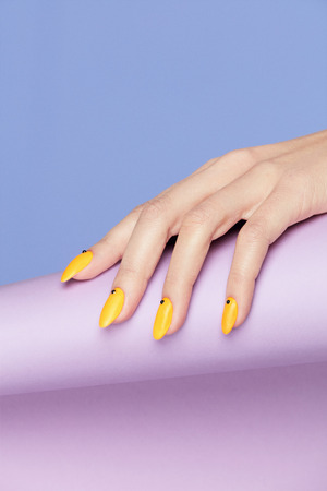 Nails Design. Hands With Bright Yellow Manicure On Violet Background. Close Up Of Female Hands With Trendy Orange Nails On Purple Background. Art Nail. High Quality Image. Banque d'images