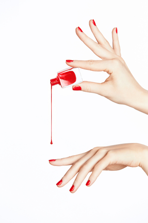 Red Nail Polish. Hand With Red Nails On White Background. Close Up Of Female Hands With Smooth Soft Skin And Bright Color Manicure Pouring Nail Polish From Bottle. High Quality Image. Banque d'images