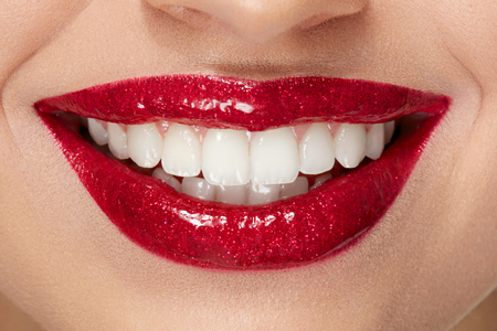 Smile With Red Lips And White Teeth. Close Up Of Smiling Womans Mouth With Red Lipstick Makeup On Plump Full Sexy Lips And Healthy White Teeth. Beauty Anf Health. High Resolution.