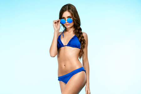 Sexy Woman In Swimsuit And Sunglasses. Portrait Of Beautiful Happy Young Female Model With Sexy Fit Body Wearing Fashionable Blue Bikini And Trendy Sunglasses. High Quality Image.