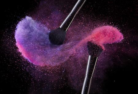 Cepillos Cosméticos Y Polvos De Explosión De Colores. Ciérrese para arriba de los cepillos del rubor suave del maquillaje que lanzan la nube del chapoteo del polvo violeta y rosado en fondo negro. Herramientas de maquillaje. Imagen de alta calidad.