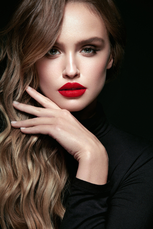Beautiful Woman With Beauty Makeup And Hairstyle. Portrait Of Young Female Model With Sexy Glamorous Face, Red Lips And Long Wavy Hair On Black Background. Cosmetics Concept. High Resolution. Foto de archivo