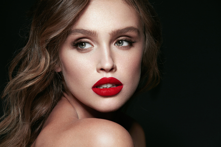 Beauty Face. Beautiful Woman With Makeup And Red Lips. Portrait Of  Young Sexy Female Model With Stylish Hairstyle, Perfect Smooth Soft Skin And Red Lipstick On Sexy Full Lips. High Resolution. Banque d'images