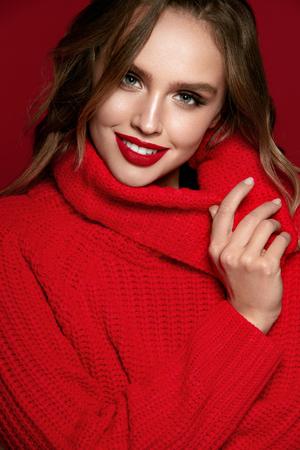 Vrouw stijl. Vrouwelijk Model Met Mooi Make-up En Kapsel. Portret van sexy jonge vrouw met lichte make-up en rode lippen in modieuze rode kleding op rode achtergrond. Mode. Afbeelding van hoge kwaliteit.