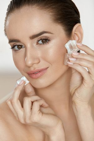 Ice On Skin. Woman Doing Face Skin Treatment Applying Ice Cubes On Fresh Healthy Facial Skin. High Quality Banco de Imagens
