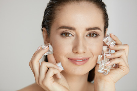Skin Beauty Care. Woman Using Ice Cubes For Face Spa Treatment On Grey Background. High Quality