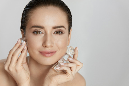 Face Skin Care. Woman Applying Ice Cubes. Beautiful Smiling Girl Doing Icing Facial Treatment On Fresh Healthy Skin. High Quality Stock fotó