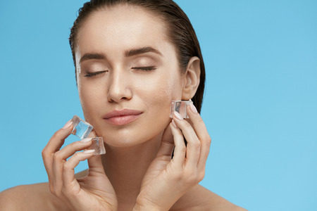 Face Skin Care. Woman Applying Ice Cubes. Beautiful Smiling Girl Doing Icing Facial Treatment On Fresh Healthy Skin. High Quality Archivio Fotografico