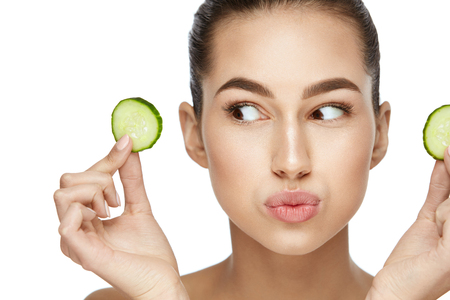 Beautiful Woman With Healthy Skin With Fresh Cucumber Slice In Hands. Stockfoto