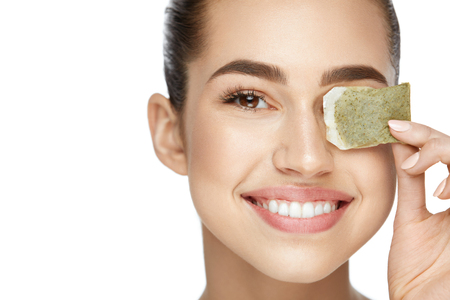 Beautiful Woman With Green Tea Bag Under Eyes On White Background.