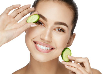 Beauty Woman Face With Fresh Skin In Spa. Female Removing Dark Circles With Cucumber Slices On White Background. High Resolution.