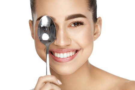 Eye Skin Care. Beautiful Woman With Healthy Skin Holding Cold Spoon Near Eye On White Background. High Resolution.