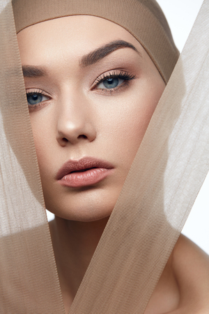 Beauty Woman Face With Even Skin Tone On Face With Pastel Pieces Of Fabric. High Quality Image.