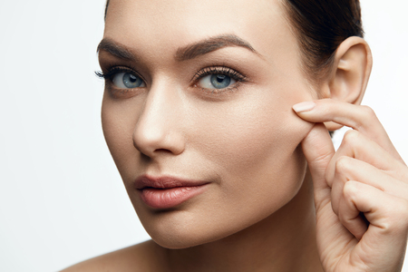Healthy Skin. Beautiful Woman With Beauty Face Pulling Elastic Facial Skin. High Resolution. Banque d'images