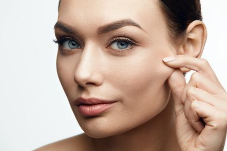 Zdrowa skóra. Piękna kobieta z piękna twarzy, ciągnąc elastyczną skórę twarzy. Wysoka rozdzielczość.