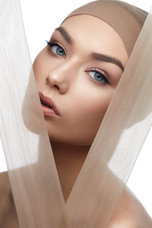 Beauty Woman Face With Even Skin Tone Foundation With Pastel Pieces Of Fabric. High Resolution.