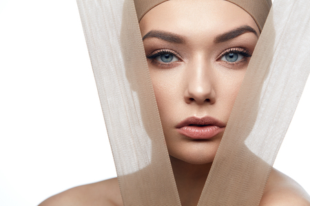 Skin Care Beauty. Woman With Beautiful Face, Natural Makeup And With Beige Fabric. High Resolution. Stock Photo