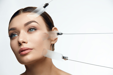 Beauty Woman Face During Face Skin Lift Treatment On White Background. High Resolution. Foto de archivo
