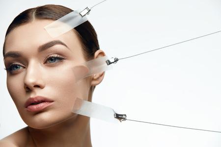 白い背景に顔の皮膚リフト治療中に美容女性の顔。高解像度。
